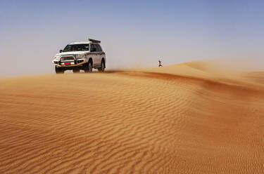 Man taking pictures in the desert, next to off-road vehicle,  Wahiba Sands, Oman - WWF05310