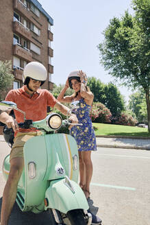 Young couple standing at vintage motor scooter - JNDF00117