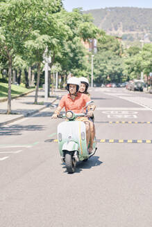 Young couple riding vintage motor scooter on urban road - JNDF00120