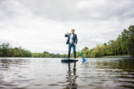 Businessman stand up paddling on a lake - JOSF03783