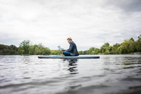 Businessman sitting on SUP board on a lake using laptop - JOSF03786