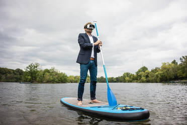 Businessman wearing VR glasses on SUP board on a lake - JOSF03792
