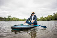 Businessman wearing VR glasses sitting on SUP board on a lake - JOSF03795