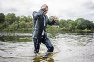 Wet businessman walking in a lake - JOSF03801