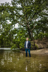 Businessman at a lonely island in a lake - JOSF03807
