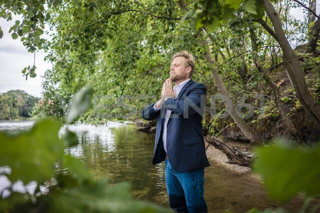 Businessman standing in a lake meditating - JOSF03813 - Joseffson/Westend61