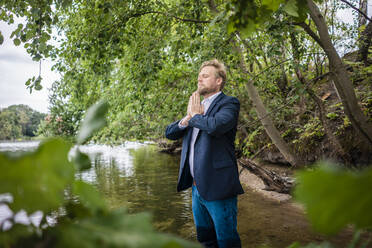 Businessman standing in a lake meditating - JOSF03813