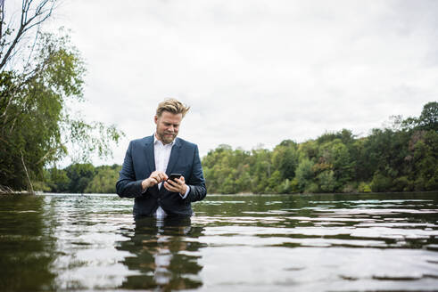 Businessman standing in a lake using cell phone - JOSF03816