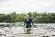 Wet businessman in a lake - JOSF03819