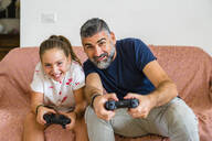 Father and daughter playing video game on couch at home - MGIF00712