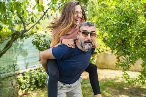 Father carrying happy daughter piggyback in garden - MGIF00721