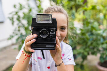 Girl taking a picture with an old-fashioned camera outdoors - MGIF00724