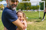 Happy father and daughter hugging on a football pitch - MGIF00733