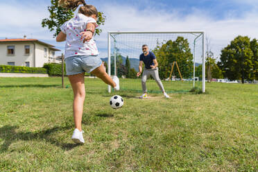 Father and daughter playing football on a meadow - MGIF00736