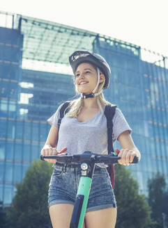 Portrait of smiling young woman with E-Scooter wearing cycling helmet, Berlin, Germany - BFRF02082