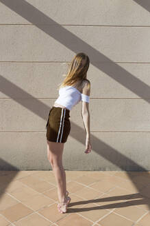 Young fashionable woman standing on tippy toes, face obscured - JPTF00322