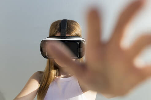 Young woman using Vr googles, reaching with her hand - JPTF00328