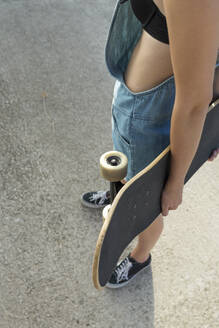 Young woman carrying skateboard, close up - JPTF00331