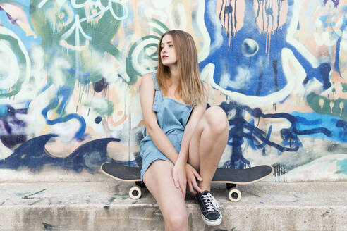 Young woman sitting on skateboard in front of graffiti - JPTF00334