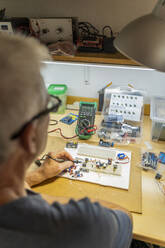 Senior man working on electronic circuits in his workshop - AFVF04020