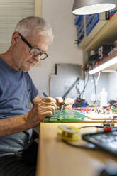 Senior man working on electronic circuits in his workshop - AFVF04023