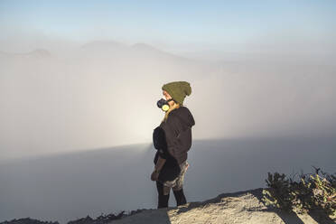 Young woman with respirator mask standing at the edge of volcano Ijen, Java, Indonesia - KNTF03604