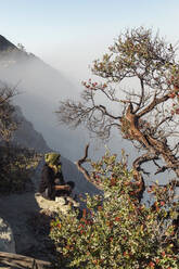 Woman with respirator mask sitting at volcano Ijen, Java, Indonesia - KNTF03610