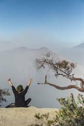 Woman with respirator mask sitting at volcano Ijen and  raising her arms, Java, Indonesia - KNTF03613
