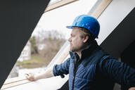 Architect looking out of window on a construction site - GUSF02657