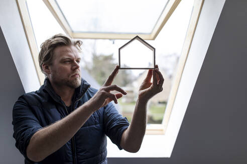 Architect looking through wooden house model - GUSF02660