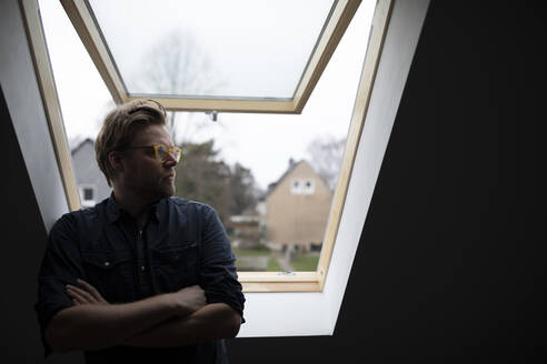 Architect standing at rooflight with arms crossed, thinking - GUSF02675