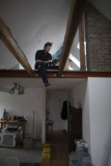 Architect working on construction sit of a loft conversion, sitting in truss - GUSF02681
