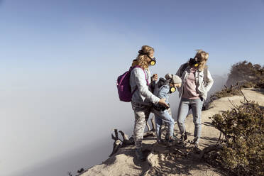 Family with respirator masks standing at the edge of volcano Ijen, Java, Indonesia - KNTF03628