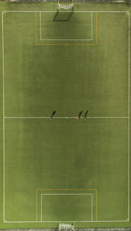 Aerial view of a football training players and shadows on synthetic surface football pitch on a summer day. - AAEF04233