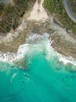 Aerial view of agitated waves hitting rock formation coast, Australia - AAEF04392