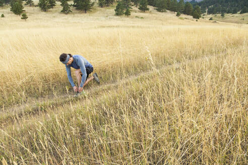 Man ties shoes on trail run in Bear Canyon above Boulder, Colorado - CAVF63396