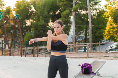 Woman runner is stretching arms in the park. Sport concept - CAVF63555
