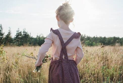 Rear view of a young girl walking through a meadow holding wildflowers - CAVF63666