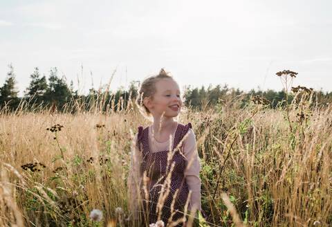 Portrait of a young girl smiling sitting in a meadow of wild flowers - CAVF63669