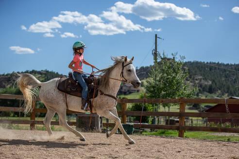 Tween girl riding horse in outdoor arena - CAVF63681