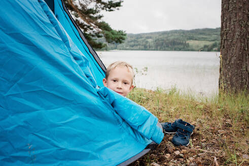 Portrait of a young blonde boy camping in a tent next to the water - CAVF63912