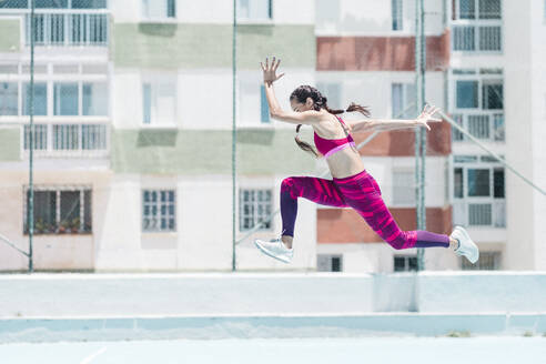 Colorful image of full body of female athlete jumping on court - CAVF64008