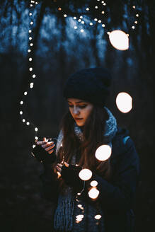 Young hipster woman holding Christmas lights while standing in park - CAVF64257