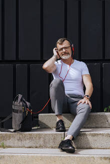 Bearded mature man sitting on steps with headphones while relaxing on a sunny day - CAVF64293