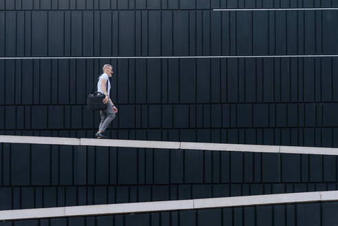Mature bearded businessman walking in the city on a wall - CAVF64308