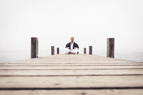 Man sitting on jetty doing yoga exercise, Lake Starnberg, Germany - WFF00090
