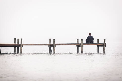 Back view of man sitting on jetty at Lake Starnberg, Germany - WFF00093