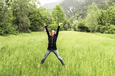 Happy young woman with red headphones jumping in the air on a meadow, Baitoni, Italy - WFF00099