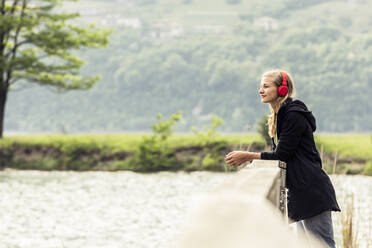 Young woman with red headphones relaxing at Lake Idro, Baitoni, Italy - WFF00102