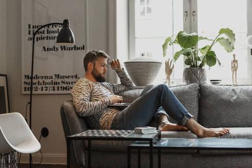 Man on sofa using laptop - JOHF02021
